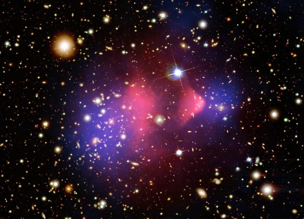 Dark matter in colliding galaxies like the Bullet Cluster show us how dark matter behaves. Credit: X-ray: NASA/CXC/CfA/M.Markevitch et al.; Lensing Map: NASA/STScI; ESO WFI; Magellan/U.Arizona/ D.Clowe et al.; Optical: NASA/STScI; Magellan/U.Arizona/D.Clowe et al.